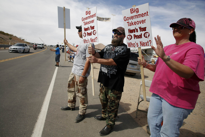 Protesters Brayden Johnson, Mike Eames and his wife Kristi Eames (L-R) wave to passing motorists in Bunkerville, Nev., as they protest efforts by the Bureau of Land Management to stop cattle from grazing on federal land. (Jim Urquhart/Reuters)
