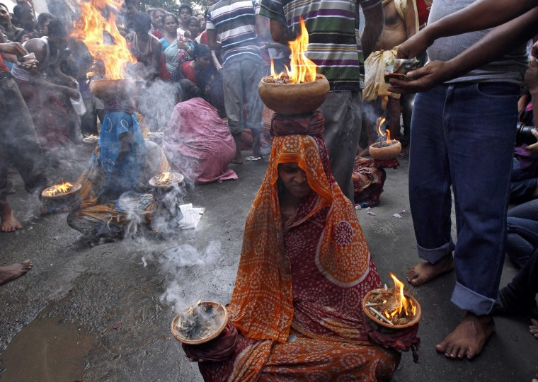 Women hold earthen pots with fire as they worship Sheetala Mata, the Hindu goddess of smallpox, during the Sheetala Puja in Kolkata. During the Puja, women fast for the whole day to pray for the betterment of their family and society. (Rupak De Chowdhuri/Reuters)