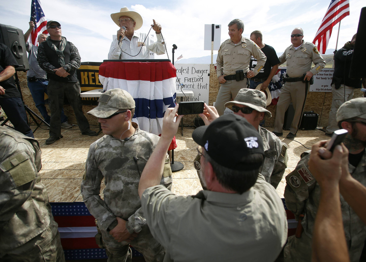 Rancher Cliven Bundy talks from a stage stage as Clark County Sheriff Douglas Gillespie stands beside him in Bunkerville, Nev. Gillespie announced the Bureau of Land Management was ceasing its cattle roundup operation. (Jim Urquhart/Reuters)
