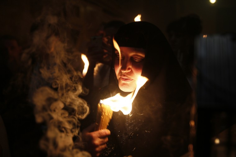 A Christian Orthodox worshipper with a candle lit from the 'Holy Fire' as thousands gather in the Church of the Holy Sepulchre in Jerusalem's old city the eve of the Orthodox Easter. Believers hold that the fire is miraculously sent from heaven to ignite candles held by the Greek Orthodox patriarch in an annual rite dating back to the 4th century that symbolises the resurrection of Jesus. (Gali Tibbon/AFP/Getty Images)