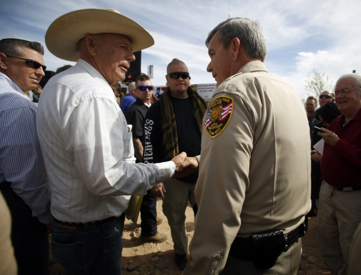 Rancher Cliven Bundy greets Clark County Sheriff Douglas Gillespie in Bunkerville, Nev. Gillespie announced the Bureau of Land Management was ceasing its cattle roundup operation. Bundy, a rancher who has illegally grazed his herd on public lands for decades, and his supporters were in a standoff stemming from Bundy's belief thathis right to graze the land predates the federal government's management of it. (Jim Urquhart/Reuters)