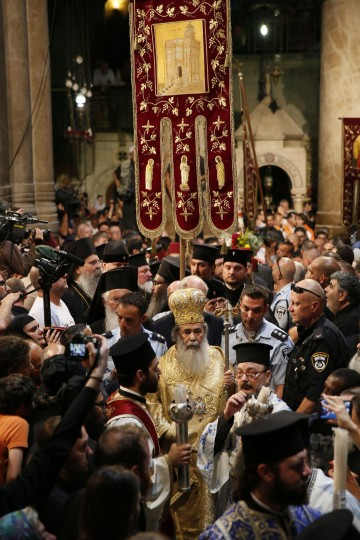 """Greek Orthodox Patriarch of Jerusalem, Theophilos III leads the procession as thousands gather in the Church of the Holy Sepulchre in Jerusalem's old city during the """"Holy Fire"""" ceremony on the eve of the Orthodox Easter. Believers hold that the fire is miraculously sent from heaven to ignite candles held by the Greek Orthodox patriarch in an annual rite dating back to the 4th century that symbolizes the resurrection of Jesus.(Gail Tibbon/AFP/Getty Images)"""