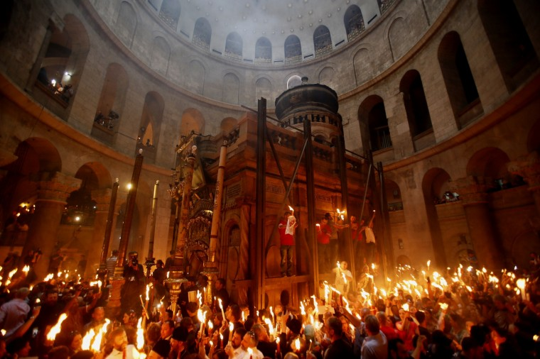 Christian Orthodox worshippers hold up candles lit from the 'Holy Fire' as thousands gather in the Church of the Holy Sepulchre in Jerusalem on the eve of the Orthodox Easter. Believers hold that the fire is miraculously sent from heaven to ignite candles held by the Greek Orthodox patriarch in an annual rite dating back to the 4th century that symbolizes the resurrection of Jesus. (Gali Tibbon/AFP/Getty Images)
