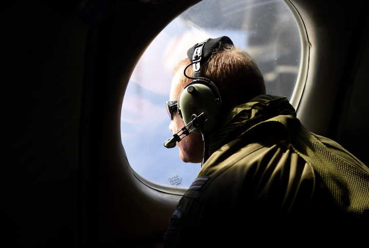 """A flight crew member aboard a Royal New Zealand Air Force P3 Orion maritime search aircraft as it flies over the southern Indian Ocean looking for debris from missing Malaysian Airlines flight MH370. Search and rescue officials in Australia are confident they know the approximate position of the black box recorders from missing Malaysia Airlines Flight MH370, Australian Prime Minister Tony Abbott said on Friday. At the same time, however, the head of the agency coordinating the search said that the latest """"ping"""" signal, which was captured by a listening device buoy on Thursday, was not related to the plane. Richard Polden/Reuters)"""