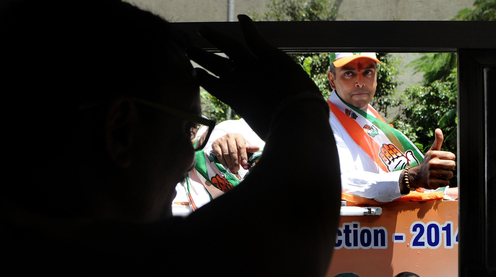 Indian Congress party candidate Milind Deora acknowledges the greetings of a bus passenger during an election roadshow in Mumbai. India's 814-million-strong electorate is voting in the world's biggest election, which is set to sweep the Hindu nationalist opposition to power at a time of low growth, anger over corruption and warnings about religious unrest.(Indranil Mukherjee/AFP/Getty Images)