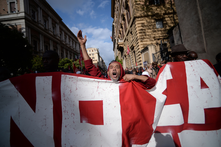 Demonstrations in Rome against austerity measures included a protest march against high housing costs and joblessness as a result of Italy's long economic slowdown. The procession made its way peacefully through central Rome until a more violent element wearing helmets started throwing objects at police (Filippo Monteforte/AFP/Getty Images)