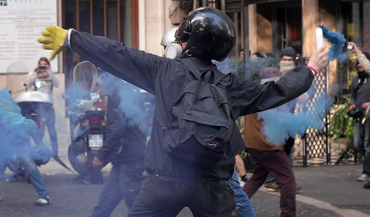 A protestor throws a flare at police on the sidelines of an anti-austerity demonstration in Rome. The protest, made up of workers and students against austerity, started peacefully, but turned violent when the group reached the Department for Industry building in the heart of the city. (Filippo Monteforte/AFP/Getty Images)