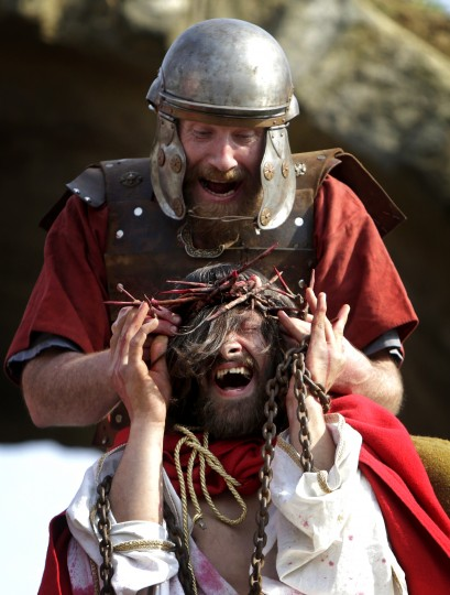 """An actor portraying a Roman soldier puts a crown of thorns on the head of an actor portraying Jesus during """"the Passion of Christ."""" The play commemorates the crucifixion of Jesus as a part of Easter festivities in the north Bohemian city of Ceska Lipa, Czech Republic. (David W Cerny/Reuters)"""