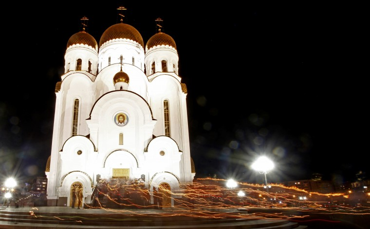 People walk with lighted candles around the Church of the Nativity during an Orthodox Easter service in Russia's Siberian city of Krasnoyarsk. (lya Naymushin/Reuters)