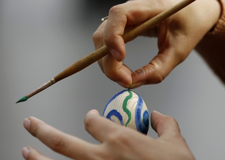 A Ukrainian woman paints a wooden egg on the eve of Easter ahead of midnight mass in Luhansk, eastern Ukraine. The Ukrainian government said it will not attack pro-Russian separatists over the Easter weekend as its U.S. ally threatened Moscow with new sanctions if it fails to persuade the militants to surrender. (Vasily Fedosenko/Reuters)