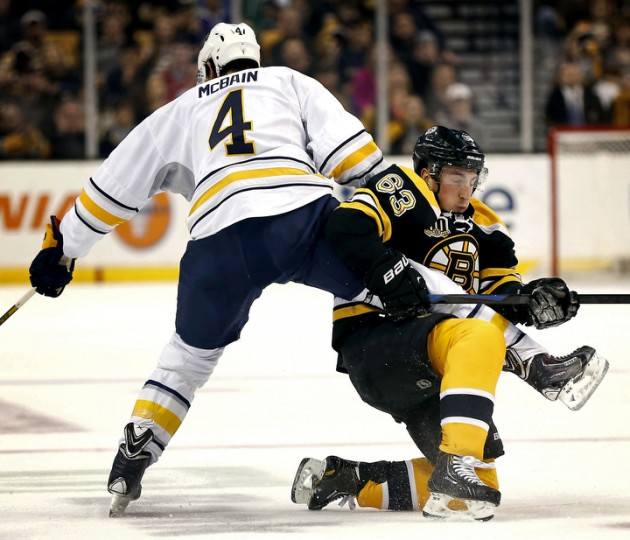 Boston Bruins left wing Brad Marchand (63) collides with Buffalo Sabres defenseman Jamie McBain (4) during the first period of their game at TD Garden. (Winslow Townson/USA Today Sports
