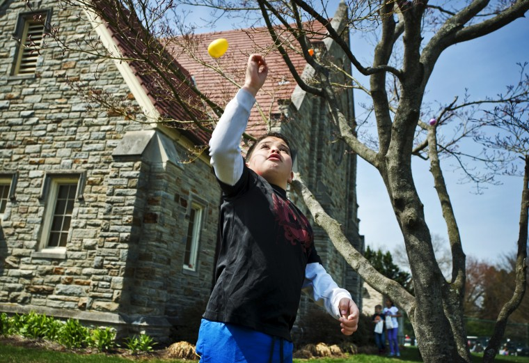 Steven Spinoza. 9, knocks a plastic Easter egg from a tree in front of St. Paul's Lutheran Church. The Catonsville church held its annual Easter Event and Hunt that is open to anyone. (Christopher T. Assaf/Baltimore Sun)