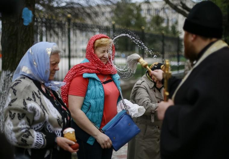A Ukrainian Orthodox priest splashes holy water on believers before an Easter service in the eastern Ukrainian town of Slaviansk. (Gleb Garanich/Reuters)
