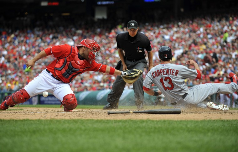 St. Louis Cardinals third baseman Matt Carpenter (13) scores in the seventh inning as Washington Nationals catcher Sandy Leon (41) cannot hold onto the ball at Nationals Park. The Cardinals defeated the Nationals 4-3. Joy R. Absalon/USA Today Sports)