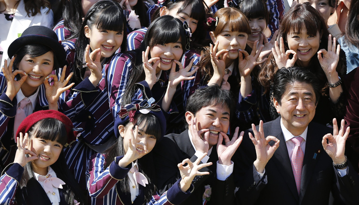Japan's Prime Minister Shinzo Abe (front row right) poses with a group of entertainers, including members of the girls' pop group HKT48during a cherry blossom viewing party at Tokyo's Shinjuku Gyoen park. Thousands of people including entertainers, athletes and politicians were invited to the annual party hosted by Abe. (Issei Kato/Reuters)