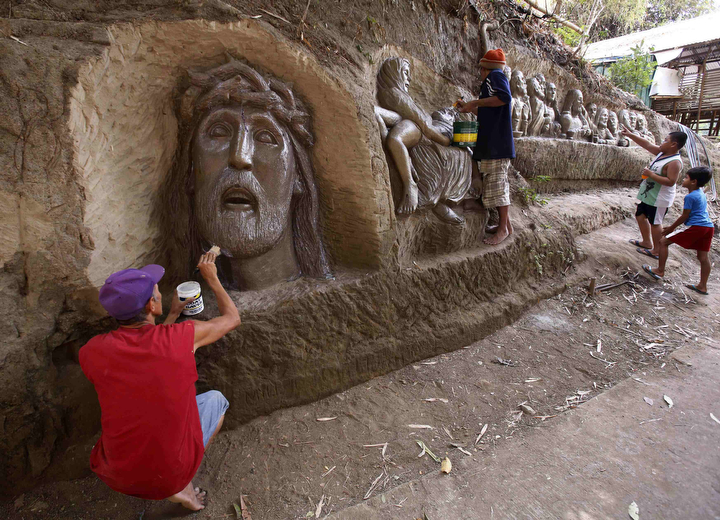 Sculptor Val Suarez and his brother Oca apply varnish to a religious sculpture depicting Jesus Christ carved into a hillside south of Manila. The Suarez brothers started sculpting different religious images on the hillside last month to commemorate the season of Lent, attracting numerous visitors from around the Philippines. (Romeo Ranoco/Reuters)