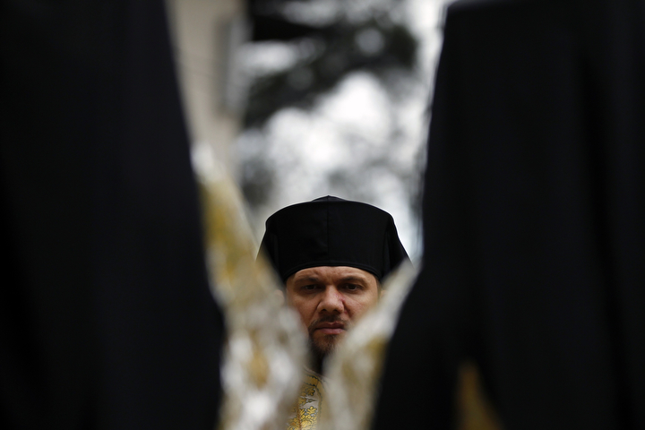 A priest attends a pilgrimage ahead of Orthodox Palm Sunday in Bucharest. Palm Sunday commemorates Jesus Christ's triumphant entry into Jerusalem before his crucifixion. Romania's Christian Orthodox majority will celebrate Easter April 20 together with Catholic believers.(Bogdan Cristel/Reuters)