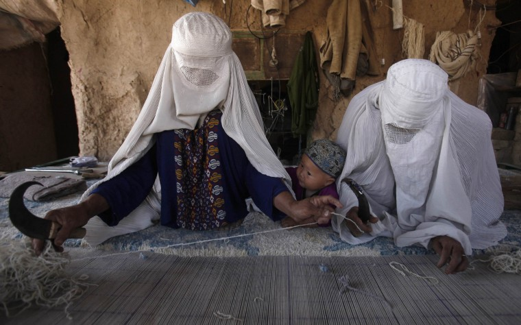 Ethnic Hazara Afghan women weave a carpet at a makeshift workshop at their house in Khorasan Refugee Camp, on the outskirts of Peshawar. Carpet-making started at the camp in 1982, when refugees fled the war in Afghanistan to take refuge in Pakistan. The carpet weavers, who are employed by contractors, are paid between 3,000 Pakistani rupees ($31) to 10,000 rupees ($103) per square metre, depending on the quality of the craftsmanship. The carpets, which can each take up to 60 days to complete, are then exported to buyers from the West and the Gulf. (Fayaz Aziz/Reuters)
