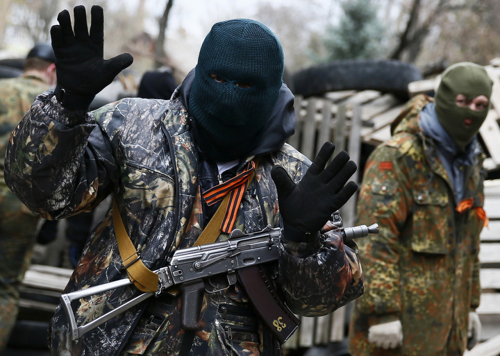 An armed man gestures in front of the police headquarters in Slaviansk, Ukraine. At least 20 armed militants, wearing mismatched camouflage outfits, took over the police and security services headquarters in the eastern city of Slaviansk seizing hundreds of handguns. (Gleb Garanich/Reuters)