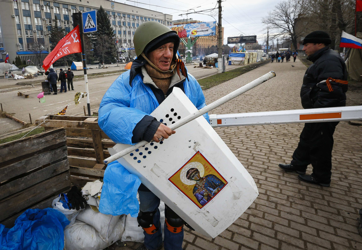 A pro-Russian protester at a barricade in front of the seized office of the SBU state security service in Luhansk, in eastern Ukraine. Ukraine's prime minister offered Friday to boost local powers in the regions in an effort to undercut pro-Russia separatists who have occupied official buildings in Russian-speaking cities in eastern Ukraine. (Shamil Zhumatov/Reuters)