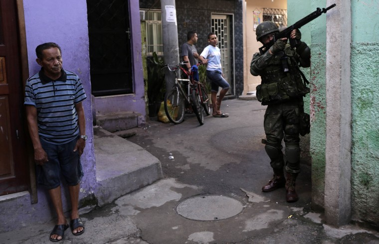 A Brazilian Army soldier patrols the Mare slums complex in Rio de Janeiro where they have taken control of security operations. The federal troops are helping to quell a surge in violent crime following attacks by drug traffickers on police posts in three slums on the north side of the city, government officials said. Less than three months before Rio welcomes tens of thousands of foreign soccer fans for the World Cup, the attacks cast new doubts on government efforts to expel gangs from slums using a strong police presence. The city will host the Olympics in 2016. (Ricardo Moraes/Reuters)