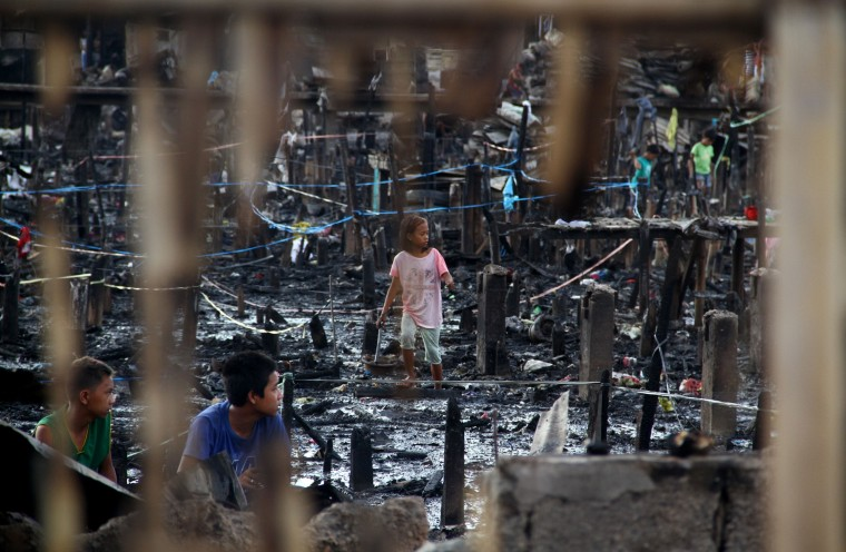 Children scavenge among twisted metal and corrugated iron sheets in the burned ruins of a slum in Davao City. A huge night fire destroyed more than a thousand homes in the slum in the Philippines' largest southern city, sending residents running for their lives, officials said. (AFP/Getty Images)