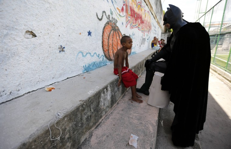 An anti-government demonstrator, dressed as comic book superhero Batman, talks with a boy during a protest by non-governmental organization Rio de Paz (Rio of Peace) at the Jacarezinho slum in Rio de Janeiro. The protest was to tell FIFA President Sepp Blatter of the conditions in the slums of Rio de Janeiro, as well as a call for the Brazilian government to improve education, health and public services so that they will achieve the same standards as the 2014 World Cup stadiums, according to the organization. (Sergio Moraes/Reuters)