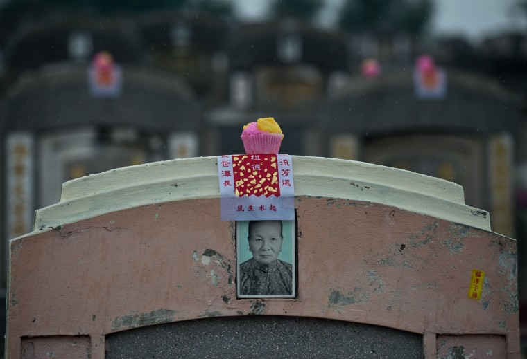 A cupcake sits atop a grave during the Qingming festival at a cemetery in Petaling Jaya. Qingming, also known as Tomb-Sweeping Day, is an annual Chinese festival to commemorate the dead. Families visit and clean the graves of their ancestors, burning incense, paper money and presenting offerings such as food, tea, wine and joss paper accessories. (Manan Vatsyayana/AFP/Getty Images)