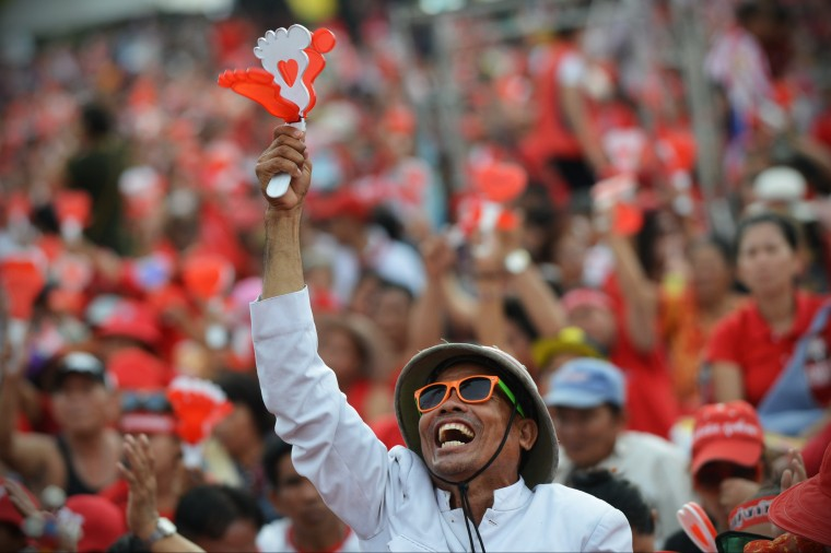 Pro-government red shirt supporters react to a speech during a rally on the outskirts of the Thai capital in Bangkok, Thailand. Tens of thousands of government supporters from across the country massed on the western suburbs of Bangkok in a show of strength, warning that any opposition attempt to remove the embattled caretaker administration of Prime Minister Yingluck Shinawatra would be met with resistance. (Rufus Cox/Getty Images)