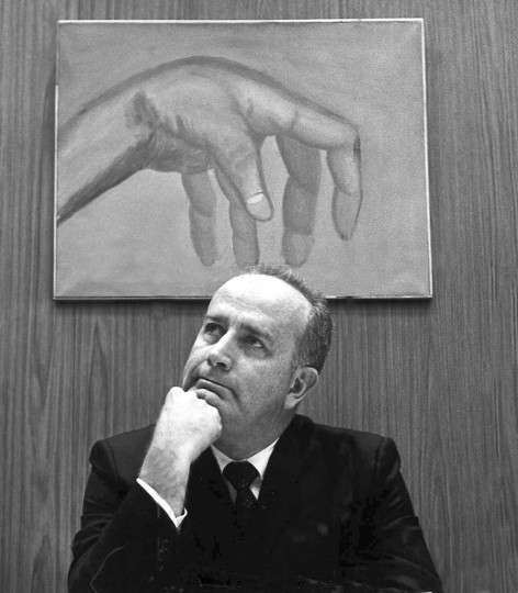 """In December 1970, then-Baltimore City Council President W. Donald Schaefer sits beneath a painting by Sister Mary Valeria Wagner, who received an art scholarship from the council. Aides to Mr. Schaefer have labeled the painting """"Tommy."""" (Lloyd Pearson/Baltimore Sun)"""