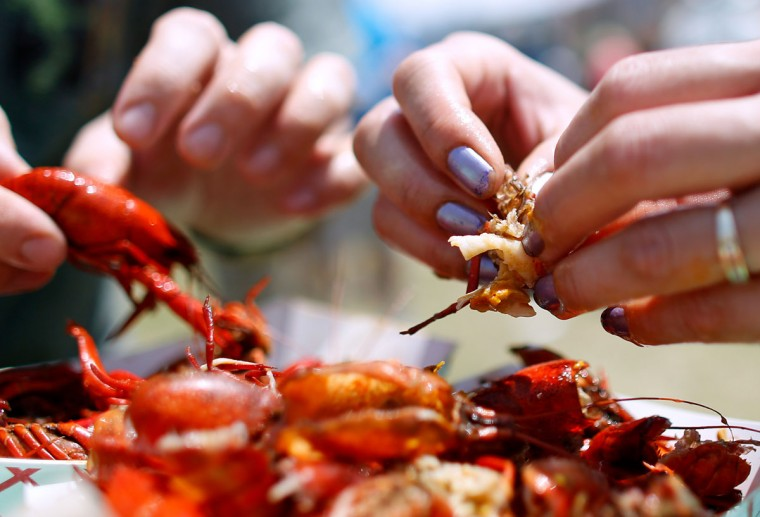 Festival goers eat crawfish during the first day of the New Orleans Jazz and Heritage Festival. (REUTERS/Jonathan Bachman)