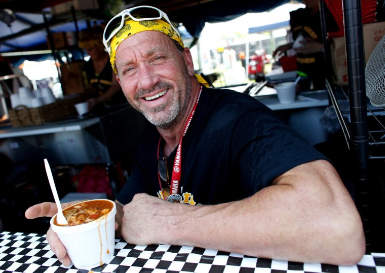 Fireman Mike poses with his alligator sauce piquant during the first day of the New Orleans Jazz and Heritage Festival. (REUTERS/Jonathan Bachman)