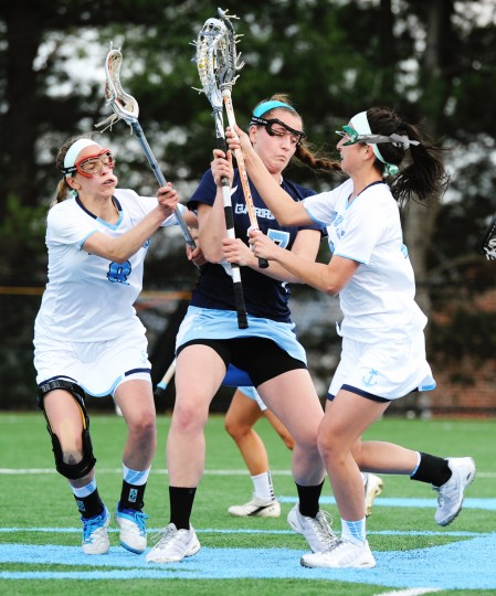 Mount de Sales' Allie Hynson, left, joins teammate Mandi Ignacio, right, in jarring the ball loose from Garrison Forest player Julie Legar during a game at Mount de Sales Academy in Catonsville on Wednesday, April 9, 2014. (Jon Sham/BSMG)