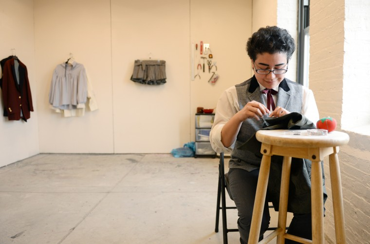 Amadeus Guchhait, a MICA student and Ellicott City native, does some needlework on an item of clothing in his studio on Friday, March 28, 2014 in Baltimore. Behind him to the left of the photo is some of his recent clothing designs. (Jon Sham/BSMG)