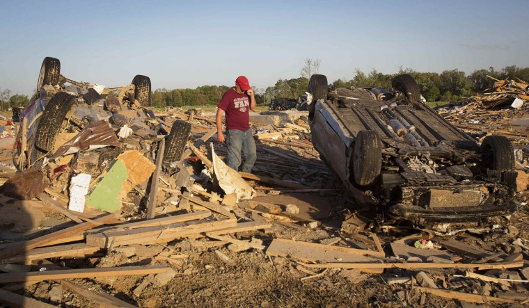 A man talks on his phone as he looks for his cat near an upturned in a suburban area following a tornado near Vilonia, Arkansas April 28, 2014. On a second day of ferocious storms that have claimed at least 19 lives in the southern United States, a tornado tore through the Mississippi town of Tupelo on Monday causing widespread destruction to homes and businesses, according to witnesses and local emergency officials. Most of the deaths from the violent storms occurred on Sunday when tornadoes tossed cars like toys in Arkansas and other states. (Carlo Allegri/Reuters photo)