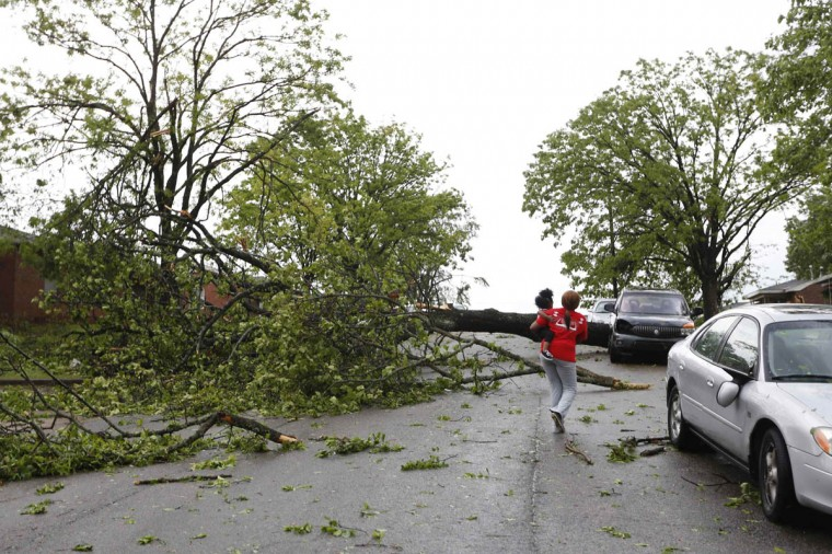 A resident walks by a downed tree along Madison Street after a tornado went through Tupelo, Mississippi April 28, 2014. On a second day of ferocious storms that have claimed at least 19 lives in the southern United States, a tornado tore through the Mississippi town of Tupelo on Monday causing widespread destruction to homes and businesses, according to witnesses and local emergency officials. (Lauren Wood/Reuters photo)