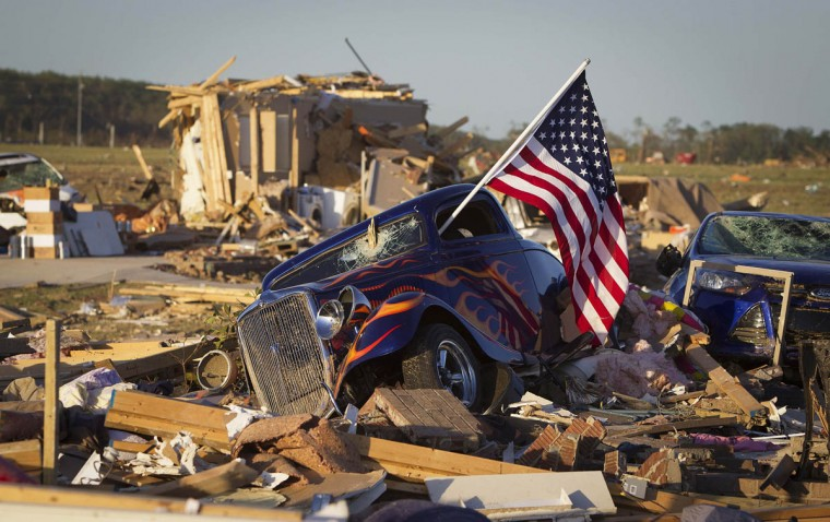 A U.S. flag sticks out the window of a damaged hot rod car in a suburban area after a tornado near Vilonia, Arkansas April 28, 2014. On a second day of ferocious storms that have claimed at least 19 lives in the southern United States, a tornado tore through the Mississippi town of Tupelo on Monday causing widespread destruction to homes and businesses, according to witnesses and local emergency officials. Most of the deaths from the violent storms occurred on Sunday when tornadoes tossed cars like toys in Arkansas and other states. (Carlo Allegri/Reuters photo)