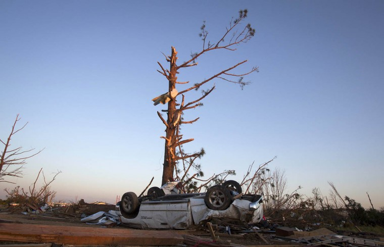 An upturned truck lies under a tree that has lost most of its branches, following a tornado near Vilonia, Arkansas, at sunset April 28, 2014. On a second day of ferocious storms that have claimed at least 19 lives in the southern United States, a tornado tore through the Mississippi town of Tupelo on Monday causing widespread destruction to homes and businesses, according to witnesses and local emergency officials. Most of the deaths from the violent storms occurred on Sunday when tornadoes tossed cars like toys in Arkansas and other states. (Carlo Allegri/Reuters photo)