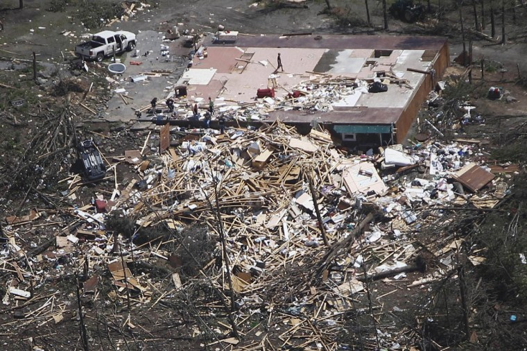Residents go through the rubble of their home one day after it was destroyed by a tornado near Vilonia, Arkansas April 28, 2014. A ferocious storm system caused a twister in Mississippi and threatened tens of millions of people across the U.S. Southeast on Monday, a day after it spawned tornadoes that killed 16 people and tossed cars like toys in Arkansas and other states. (Carlo Allegri/Reuters photo)