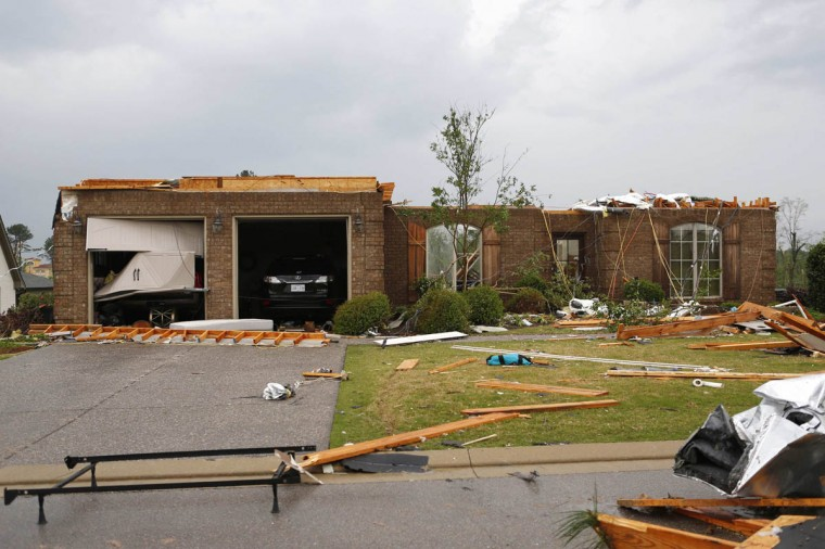 A house on Dunbarton Oaks Circle stands without its upper floor behind Lost Pizza Co. after a tornado went through the area in Tupelo, Mississippi April 28, 2014. On a second day of ferocious storms that have claimed at least 19 lives in the southern United States, a tornado tore through the Mississippi town of Tupelo on Monday causing widespread destruction to homes and businesses, according to witnesses and local emergency officials. (Lauren Wood/Reuters photo)
