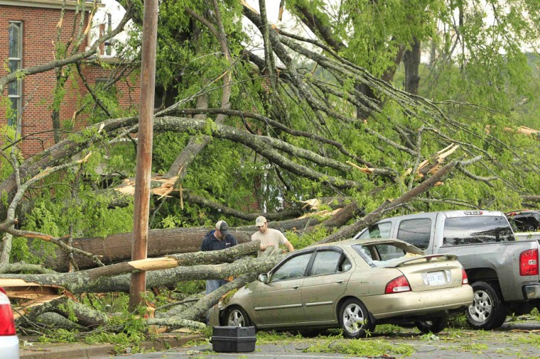 Volunteers start clearing trees off cars from a parking lot in the Joyner neighborhod after a tornado ripped through the area in Tupelo, Mississippi April 28, 2014. On a second day of ferocious storms that have claimed at least 19 lives in the southern United States, a tornado tore through the Mississippi town of Tupelo on Monday causing widespread destruction to homes and businesses, according to witnesses and local emergency officials. (Thomas Wells/Reuters photo)
