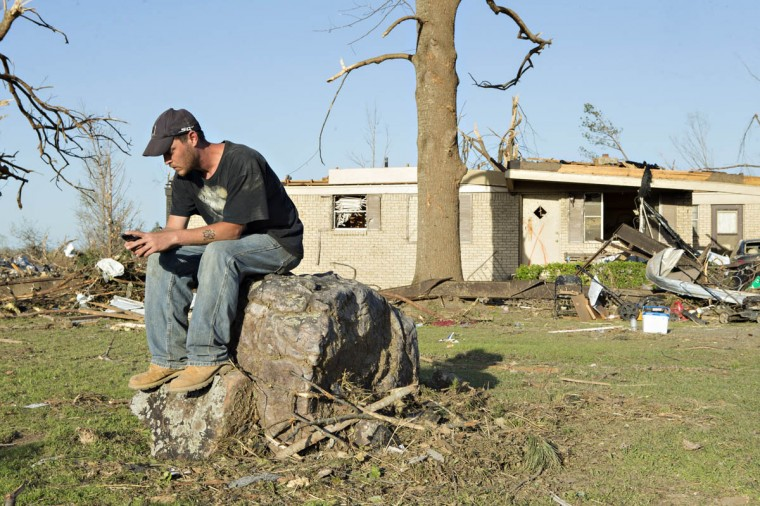 William Higgins sits on a stump outside his grandfather's house that was destroyed by a tornado yesterday that tore through the area for the second time in three years is shown, on April 28, 2014 in Mayflower, Arkansas. After deadly tornadoes ripped through the region leaving more than a dozen dead, Mississippi, Arkansas, Texas, Louisiana and Tennessee are all under watch as multiple storms over the next few days are expected. (Wesley Hitt/Getty Images)