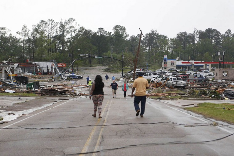 People walk down Green Street to the corner of North Gloster Street after a tornado went through Tupelo, Mississippi April 28, 2014. On a second day of ferocious storms that have claimed at least 19 lives in the southern United States, a tornado tore through the Mississippi town of Tupelo on Monday causing widespread destruction to homes and businesses, according to witnesses and local emergency officials. (Lauren Wood/Reuters photo)