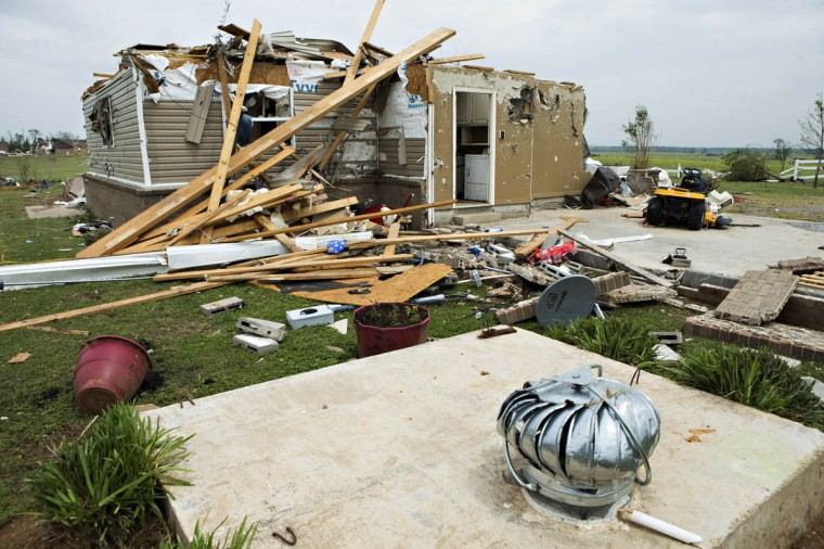 A home lies in ruins near a storm shelter in the foreground after a tornado yesterday tore through the area for the second time in three years, on April 28, 2014 in Vilonia, Arkansas. After deadly tornadoes ripped through the region, leaving more than a dozen dead, Mississippi, Arkansas, Texas, Louisiana and Tennessee are all under watch as multiple storms over the next few days are expected. (Wesley Hitt/Getty Images)