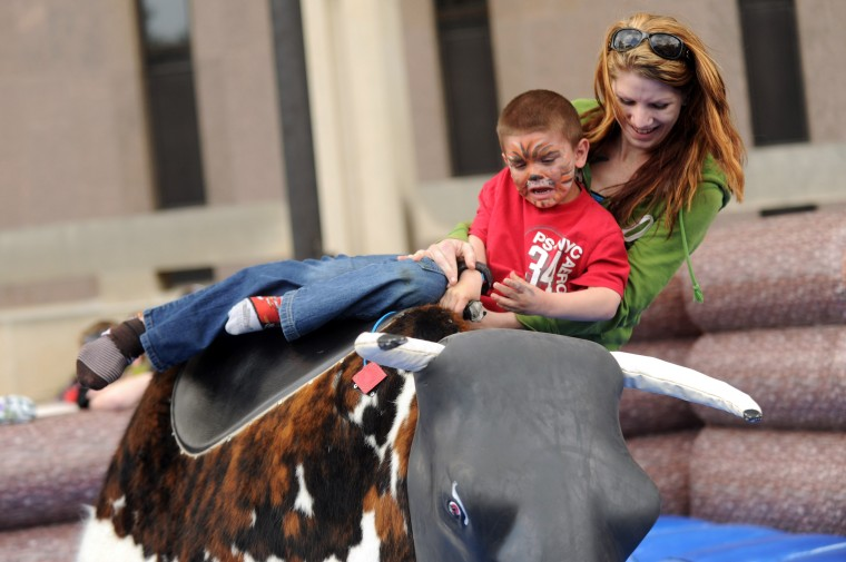 Shelby Kirby of Cockeysville tries to hang on with her 5-year-old son Vincent as they ride a mechanical bull during the Towsontown Spring Festival on Saturday, May 3. (Brian Krista/BSMG)
