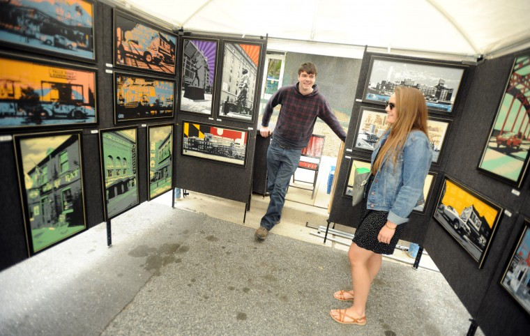 Baltimore artist Charlie Barton talks about his artwork with repeat customer Alexa Carney of Towson, right, during the Towsontown Spring Festival on Saturday, May 3. (Brian Krista/BSMG)