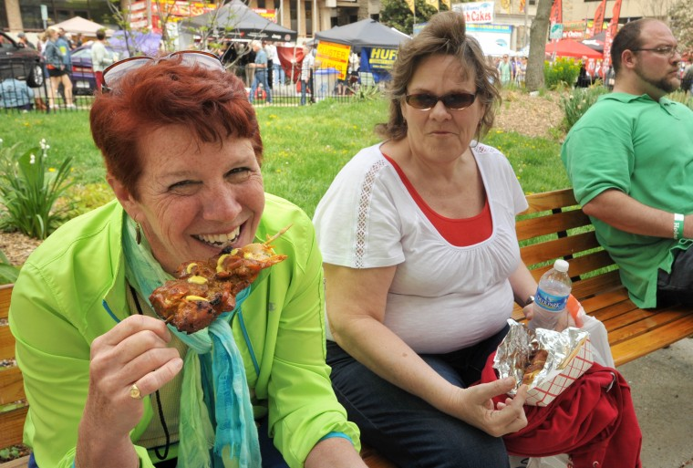 Catonsville friends Lisa Teal, left, biting into a chicken on a stick, and Chris Moxley, right, at the annual Towsontown Spring Festival. (Amy Davis/Baltimore Sun Staff)