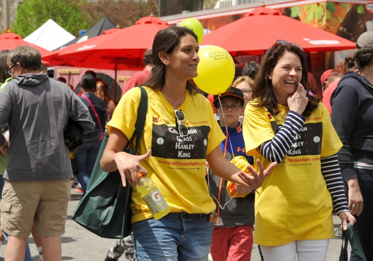 Maya Yacoub, center, and Jennifer Lazenby, right, both Towson attorneys, wear T-shirts supporting the sitting judges at the annual Towsontown Spring Festival. (Amy Davis/ Baltimore Sun Staff)