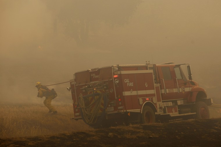 A firefighter pulls a hose into position to battle the Cocos fire on May 15, 2014 in San Marcos, California. Fire agencies throughout the state are scrambling to prepare for what is expected to be a dangerous year of wildfires in this third year of extreme drought in California. (Photo by David McNew/Getty Images)