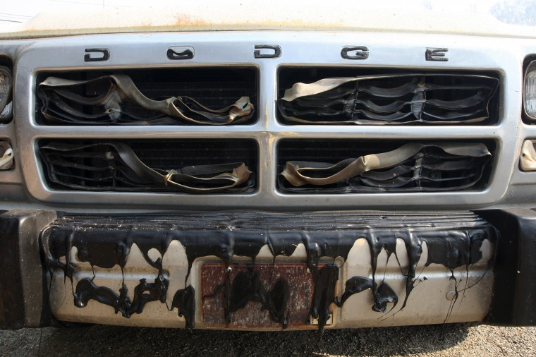 The grill of a pickup truck is left melted by the Cocos fire on May 15, 2014 in San Marcos, California. Fire agencies throughout the state are scrambling to prepare for what is expected to be a dangerous year of wildfires in this third year of extreme drought in California. (Photo by David McNew/Getty Images)